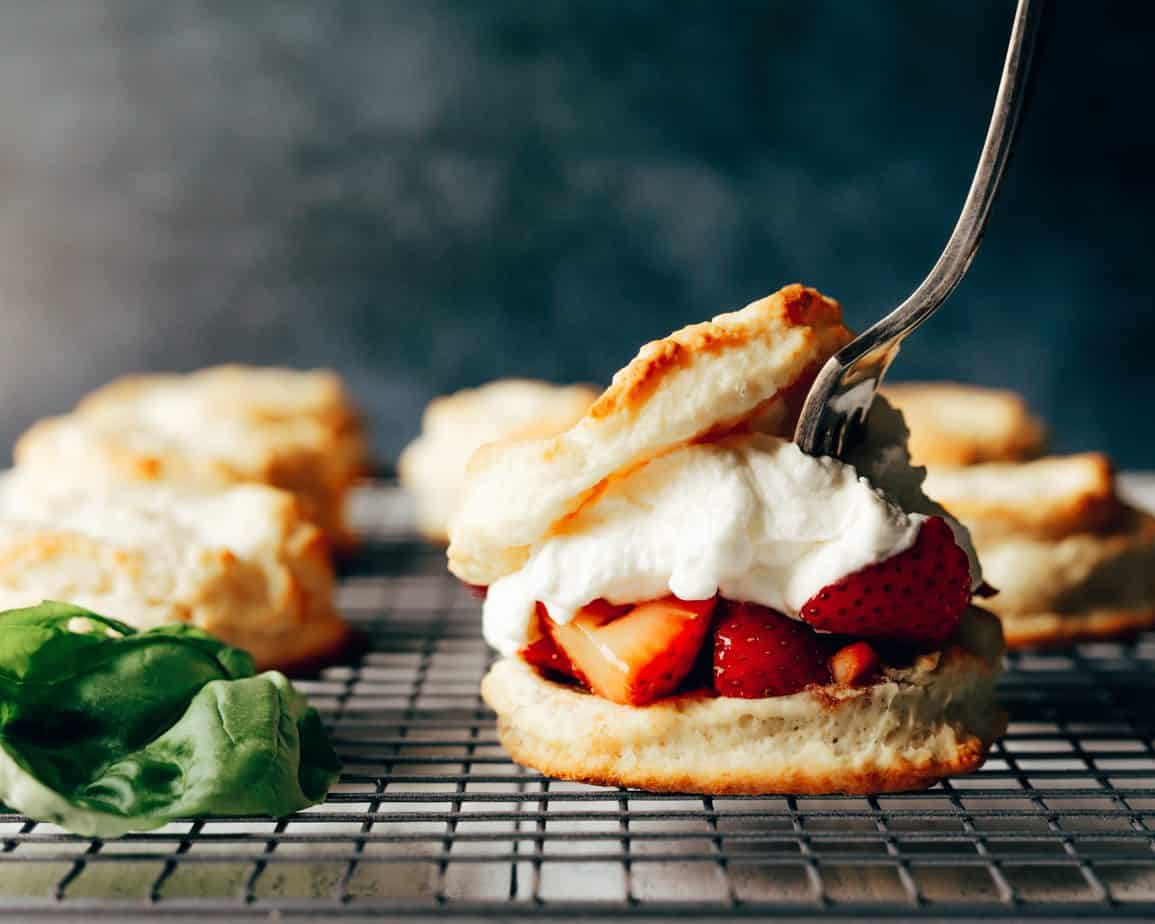A fork dives into a freshly assembled strawberry shortcake with honey and balsamic macerater strawberries