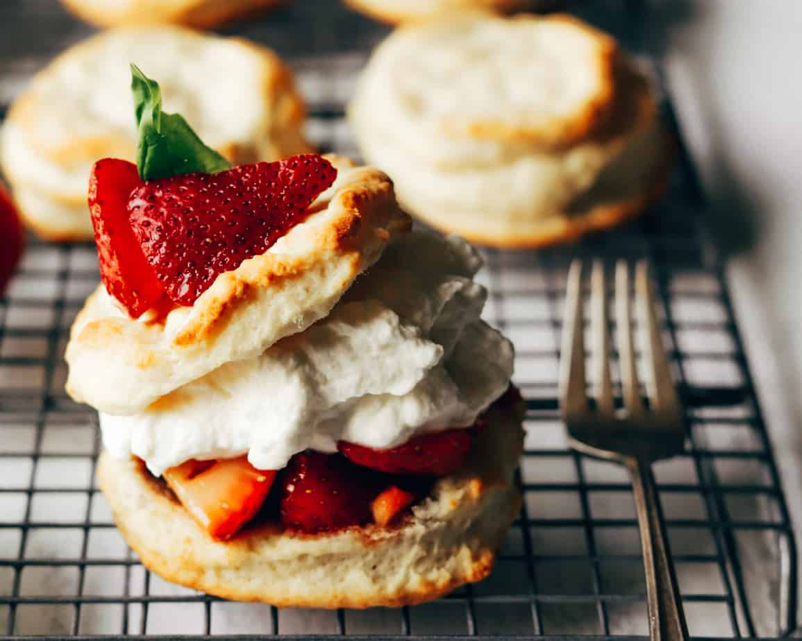 Strawberries and basil top homemade biscuits, filled with whipped cream and honey balsamic sweetened strawberry compote
