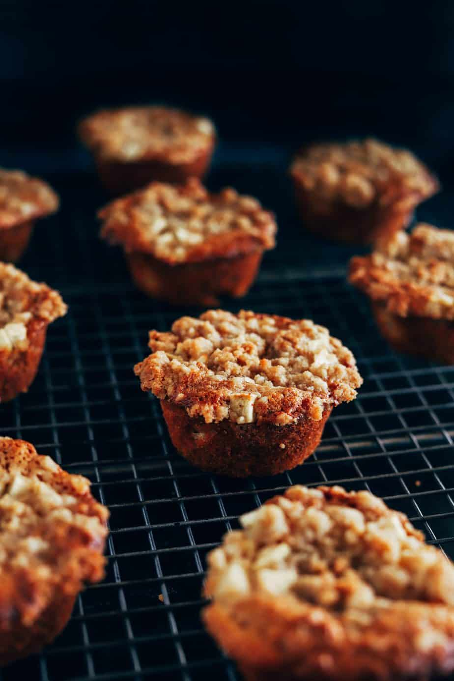 Apple muffins cooling on a rack with caramelized crumble topping