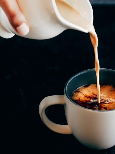 Hand pouring a white ceramic creamer of coconut cream into a freshly brewed cup of light roast coffee