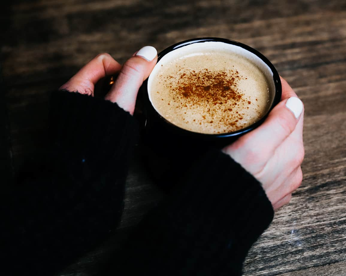 Woman with black sweater holds a cup of bulletproof coffee in a black mug sprinkled with cinnamon
