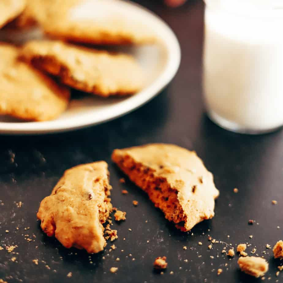 Cookie broken in half with crumbs falling onto the counter, next to a plate of freshly baked cookies and cold glass of milk in the background