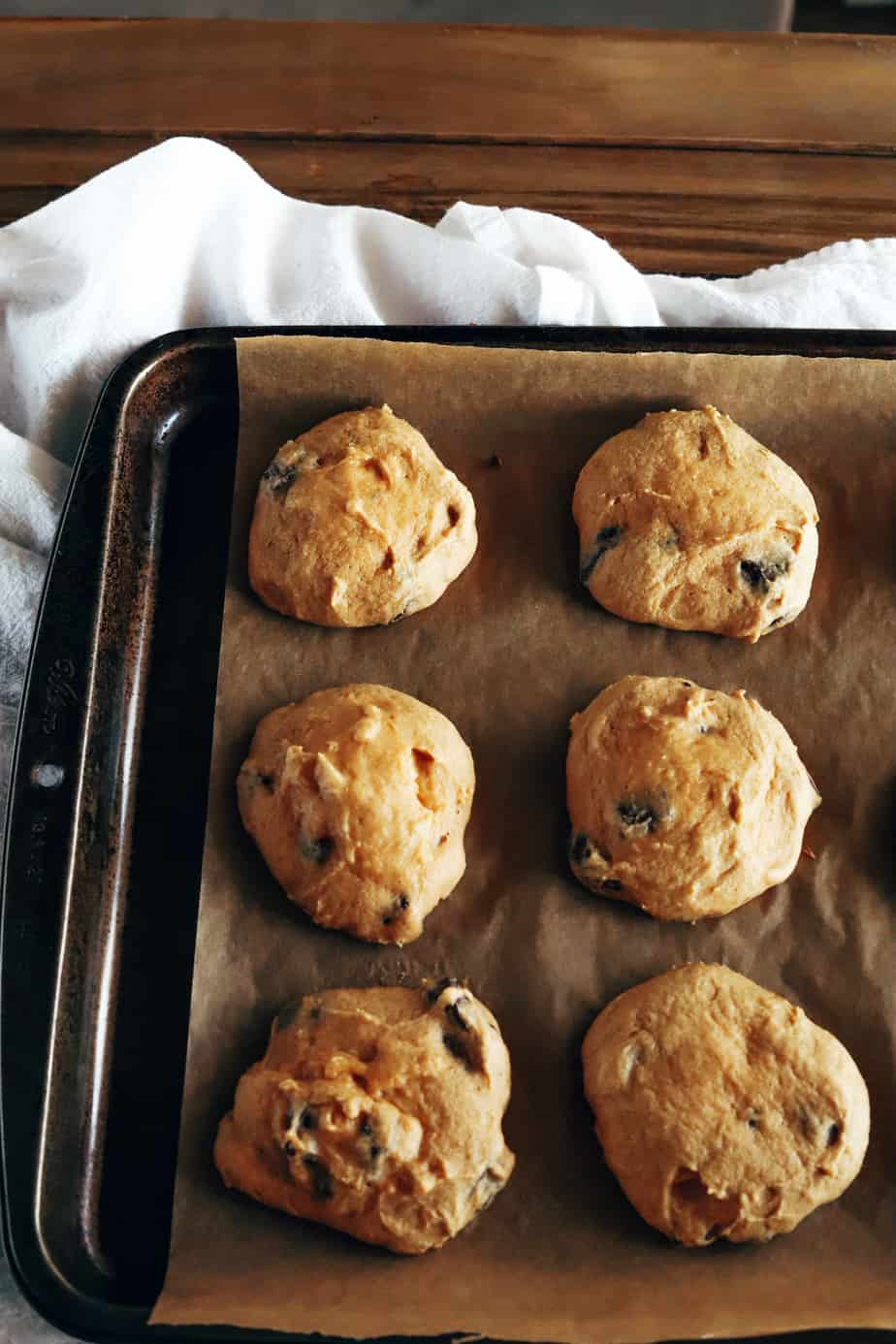 Freshly baked pumpkin muffin cookies are cooling on a baking sheet atop a white folded tea towel