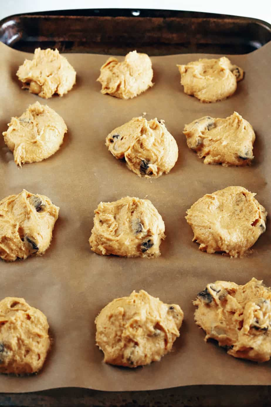 Cookie dough is scooped an arranged on a baking sheet lined with brown parchment paper