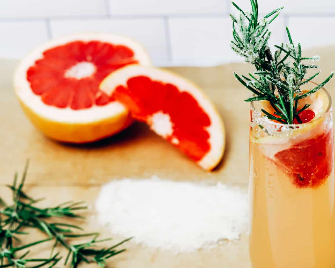 parchment paper lined with sugar, rosemary, and grapefruit for cocktail preparation