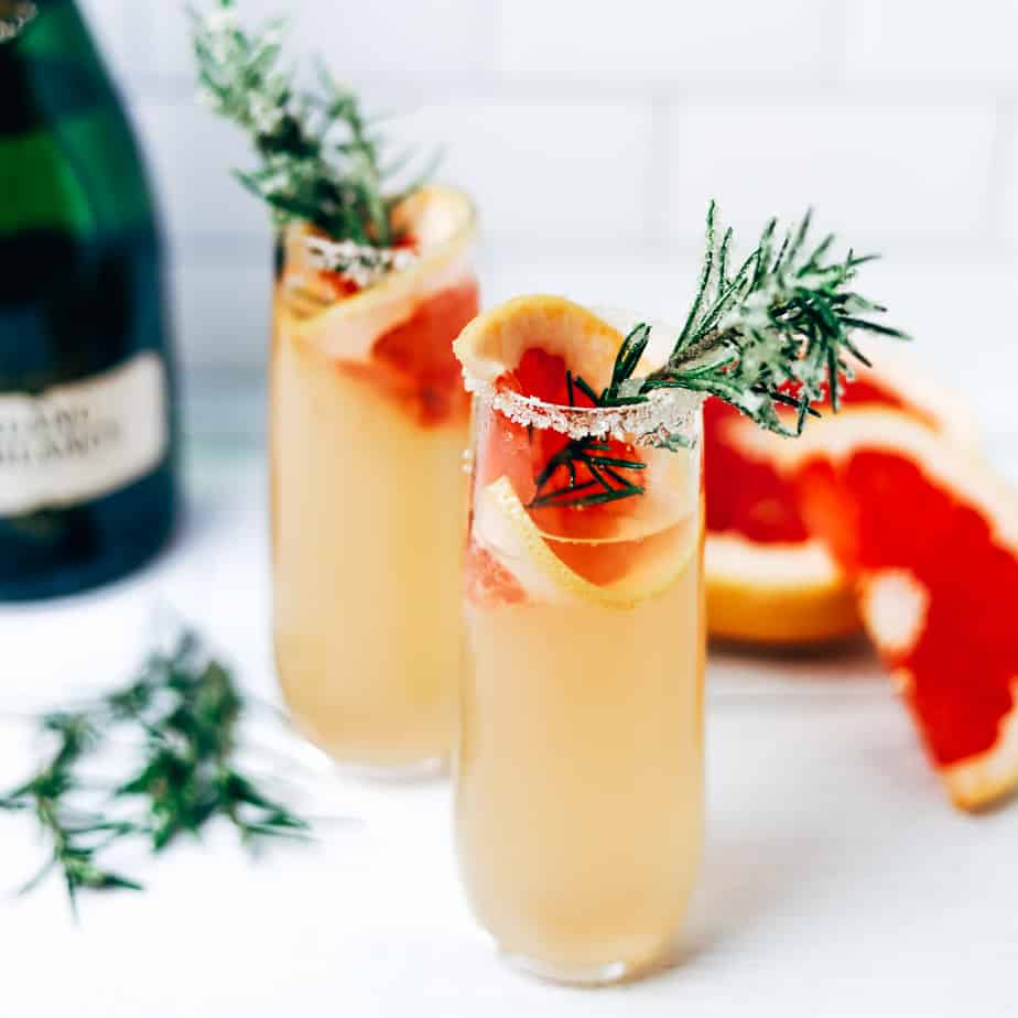 two champagne flutes with grapefruit cocktail and garnished with rosemary sprigs rolled in sparkling sugar