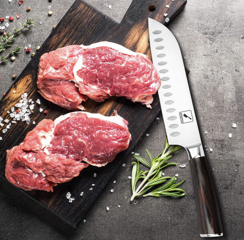 Large chef's knife on a cutting board next to a ribeye with rosemary