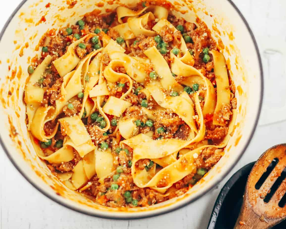 Large white pot with slow made bolognese, flat noodles, bright green peas, just stirred with the wooden spoon resting on a plate.