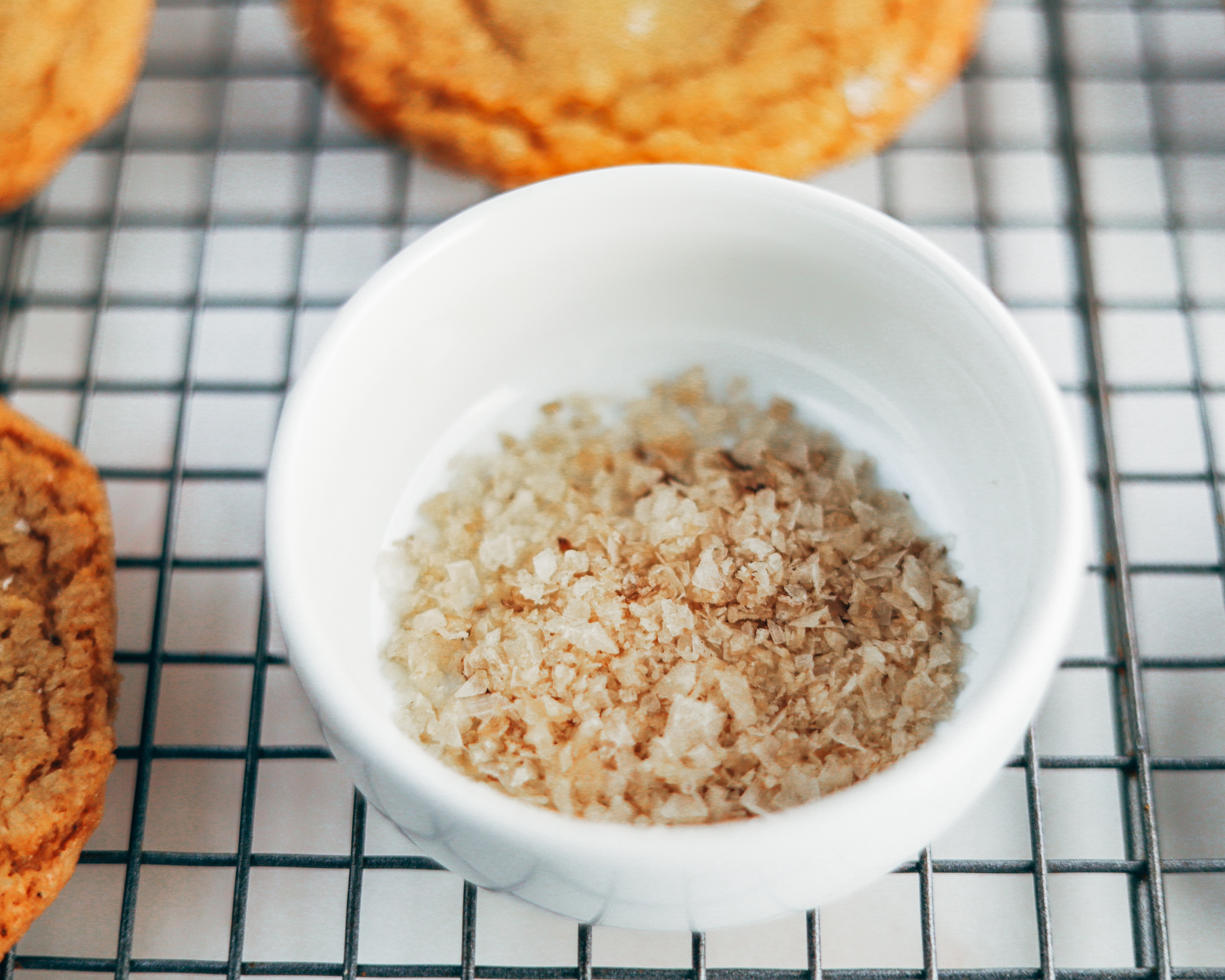 white pinch bowl holds a tablespoon of smoked sea salt flakes