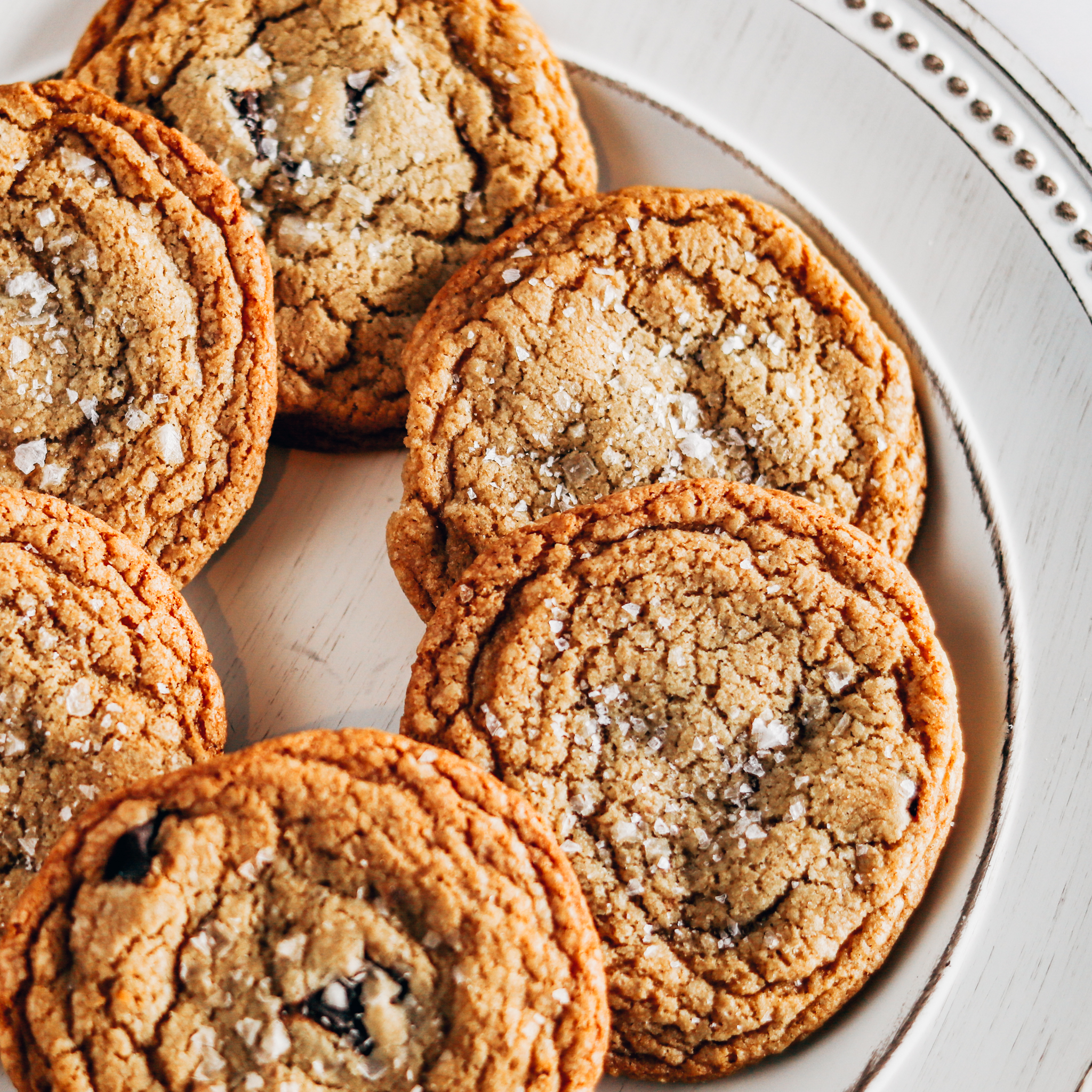 6 cookies are arranged in a circular shape on a white distressed plate on the counter top as they cool.
