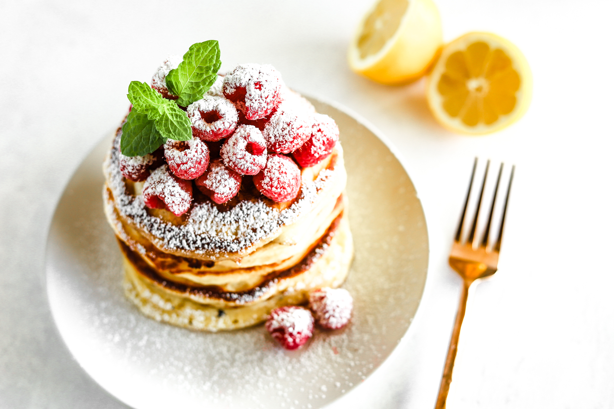 Lemon ricotta pancakes topped with raspberries and garnished with powdered sugar, mint, and paired with a rose gold fork.