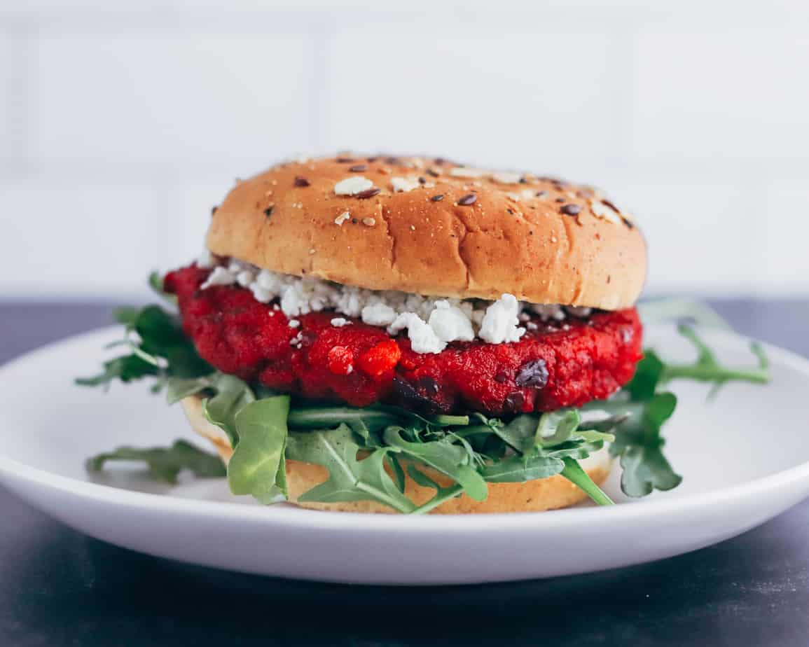 A beet burger is plated and garnished with goat cheese, arugula, topped with a seeded bun.