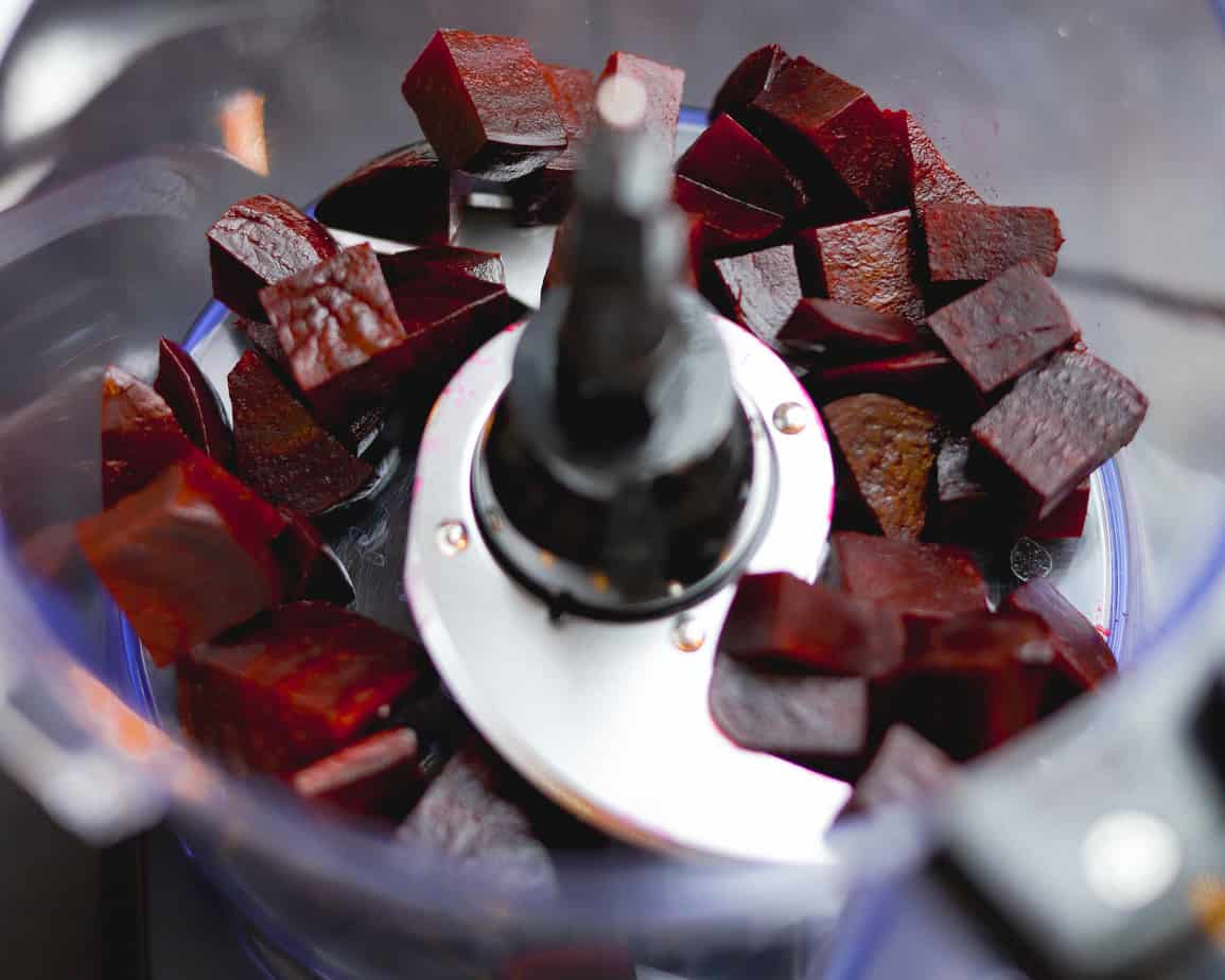 Food processor with cubed beets before pulsing into finely chopped bits.